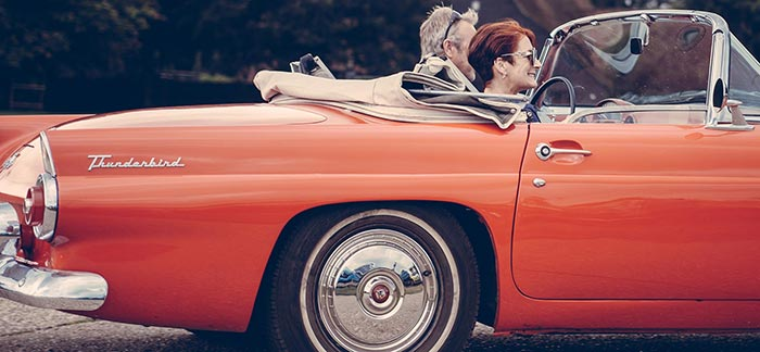 Image of retired couple in red Thunderbird convertible car for Quotacy blog: 10-Year Term Life Insurance and Retirement.