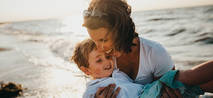 Mom with son on the beach for Quotacy blog Supplementing Term Life Insurance with Whole Life Insurance