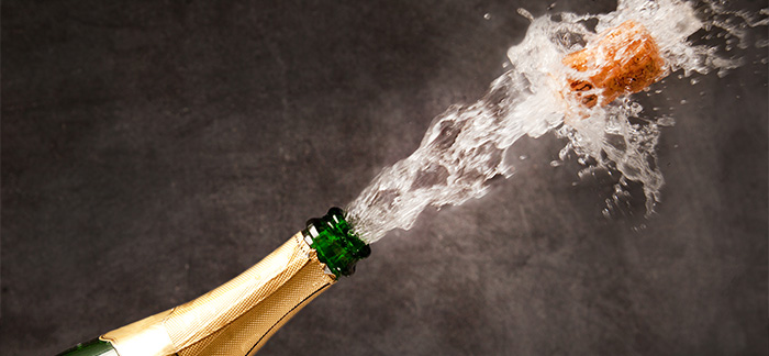 Image of champagne bottle being popped for Quotacy's first newsletter of the year