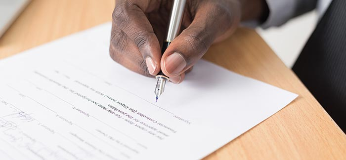man signing life insurance document for Quotacy blog end of life documents you need
