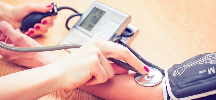 woman getting blood pressure read for Quotacy blog Demystifying Life Insurance Medical Exam