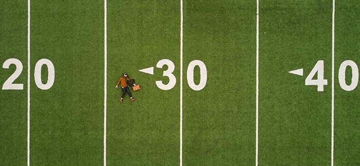 person laying on 30 yard line for Quotacy blog How Does Age Affect Life Insurance