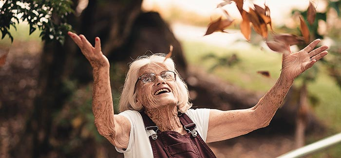 happy elderly woman throwing fall leaves for Quotacy blog How Will You Pay for Long-Term Care?