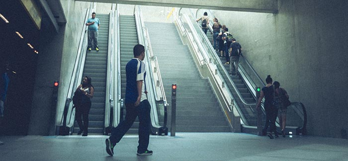 group of people on escalator for Quotacy blog Premiums for My Group Life Insurance Are Increasing What Now?