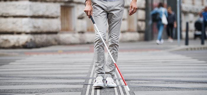 person walking with blind cane for Quotacy blog Buying Life Insurance for Blind and Hearing Impaired