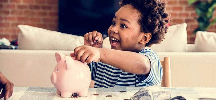 male child putting coins in piggy bank for Quotacy blog 6 Best Things to Buy During Labor Day Sales