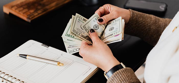 Woman counting money for Quotacy blog Audit Your Monthly Budget