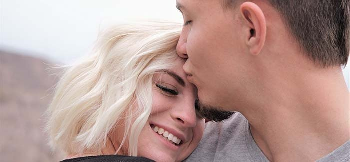 man in 20s kissing woman's forehead for Quotacy blog Is it a good idea to get life insurance in my 20s?