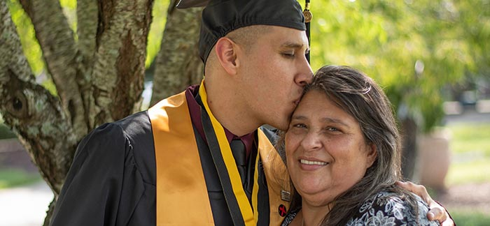 college graduate kissing his mom on the forehead for Quotacy blog My Parents Bought Life Insurance on Me as a Baby. Is It Mine Now?