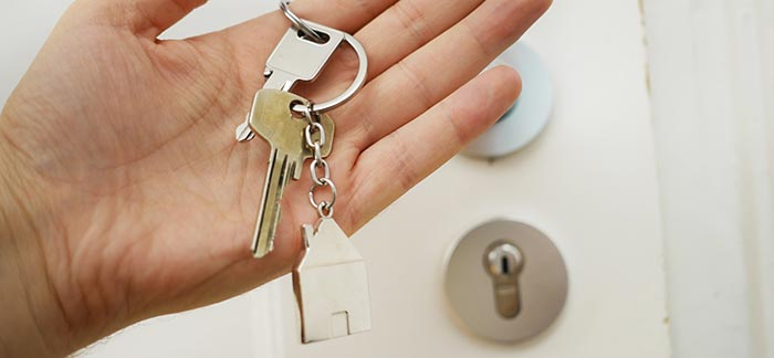 holding set of house keys for Quotacy blog Tips for Taking Advantage of Low Interest Rates
