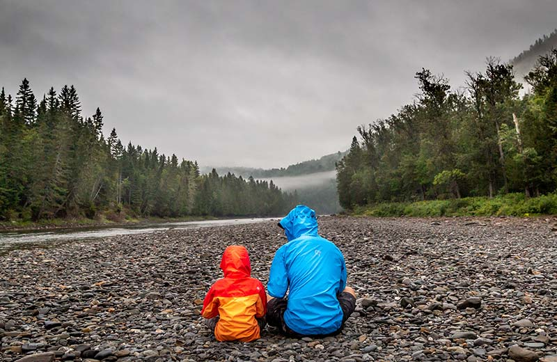 Dad and son sitting on a rocky river bed looking at the water.
