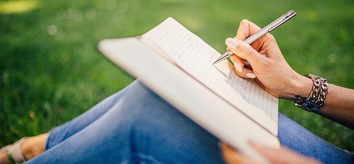 woman writing in journal for Quotacy blog how to nail this year's performance review