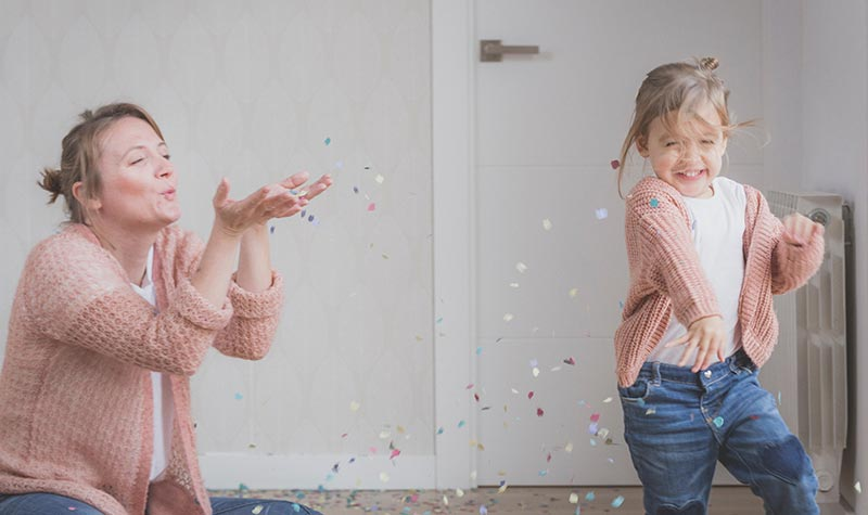 Mom and daughter playing with glitter and laughing.