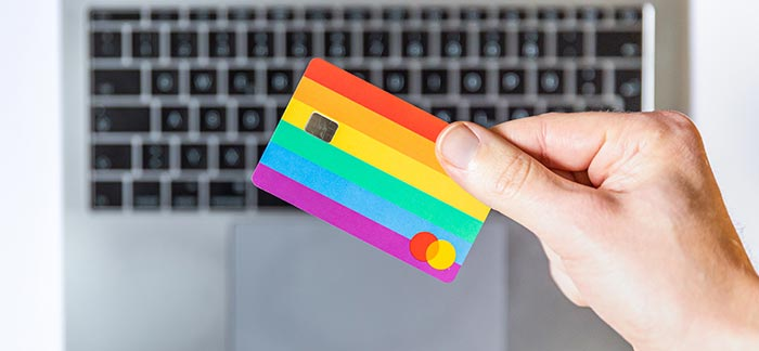 holding a credit card by a laptop for Quotacy blog how to be a smart holiday shopper