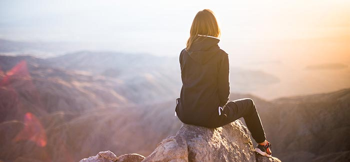 woman relaxing in nature for Quotacy blog How to Lift Your Mood - A Guide to A Positive Mindset