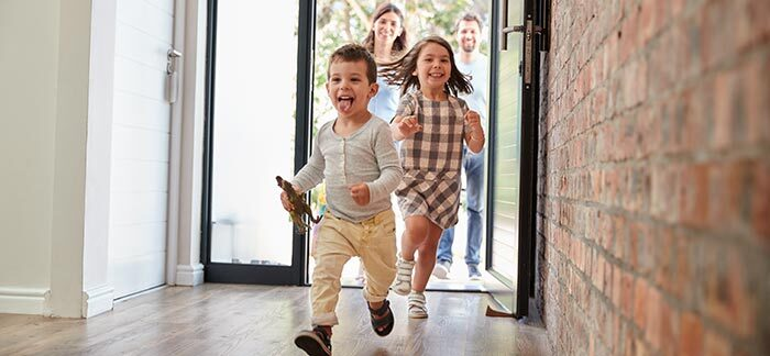 kids running through front door for Quotacy blog How much does a million dollar life insurance policy cost