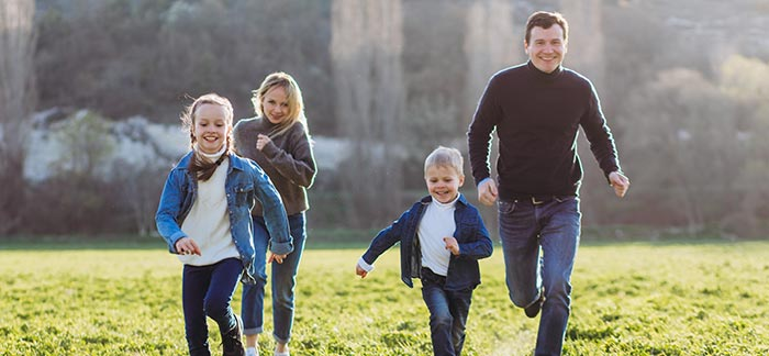 mom dad and children running for Quotacy blog cost of $100,000 life insurance policy