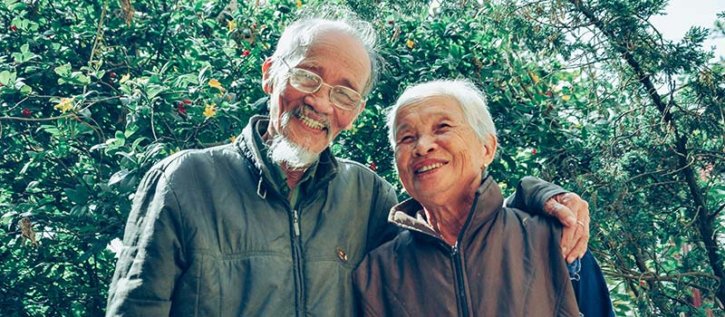 Senior couple hugging and smiling while on a walk.